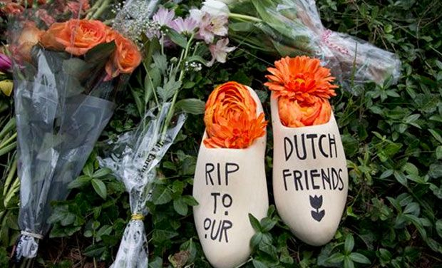 A message of sympathy for the victims of the flight MH17 disaster, is written on a wooden klomp, a traditional Dutch footwear for farmers, placed together with bouquet of flowers in front of the Netherlands Embassy in Washington, Monday, 21 July 2014