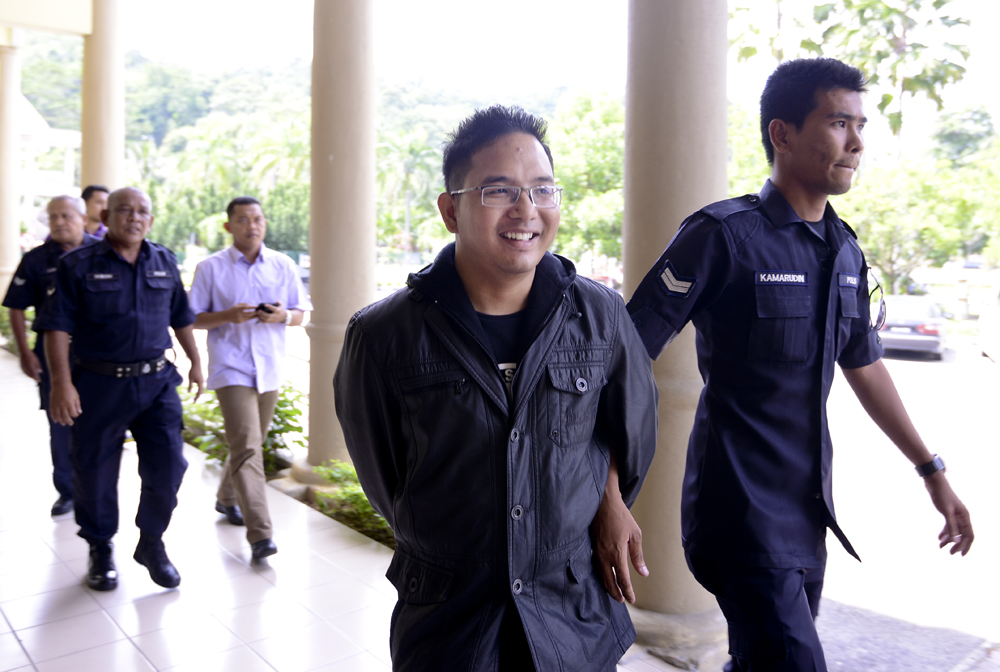Ali Abd Jalil (left) being led by a policeman at the Selayang Sessions Court today, to face a sedition charge.