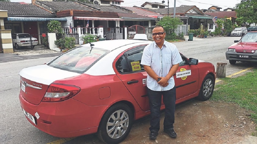 Mohd Kamil Affendy Hashim standing alongside the cab he drives