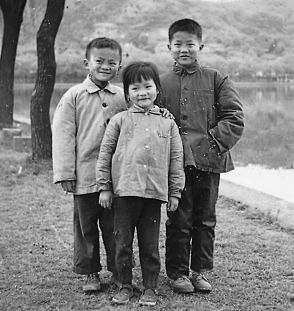 A young Jack Ma, left, with his older brother and younger sister by West Lake in Hangzhou, China.