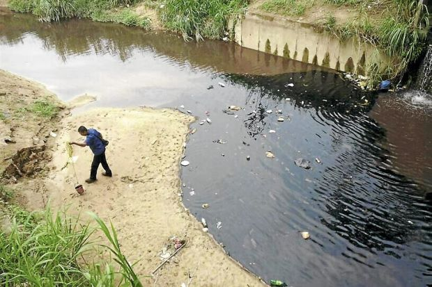 A Puncak Niaga worker inspecting the oil spill at the Sungai Selangor Phase 2 treatment plant.