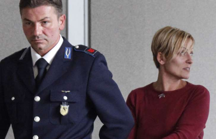 In this photo taken on Monday, Oct. 13, 2014, Daniela Poggiali is escorted by a police officer as she arrives to court in Ravenna, Italy.