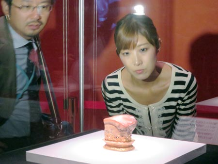 "A visitor examines the ""Meat-shaped Stone,"" one of the treasures from Taiwan's National Palace Museum, at an exhibition at the Kyushu National Museum"