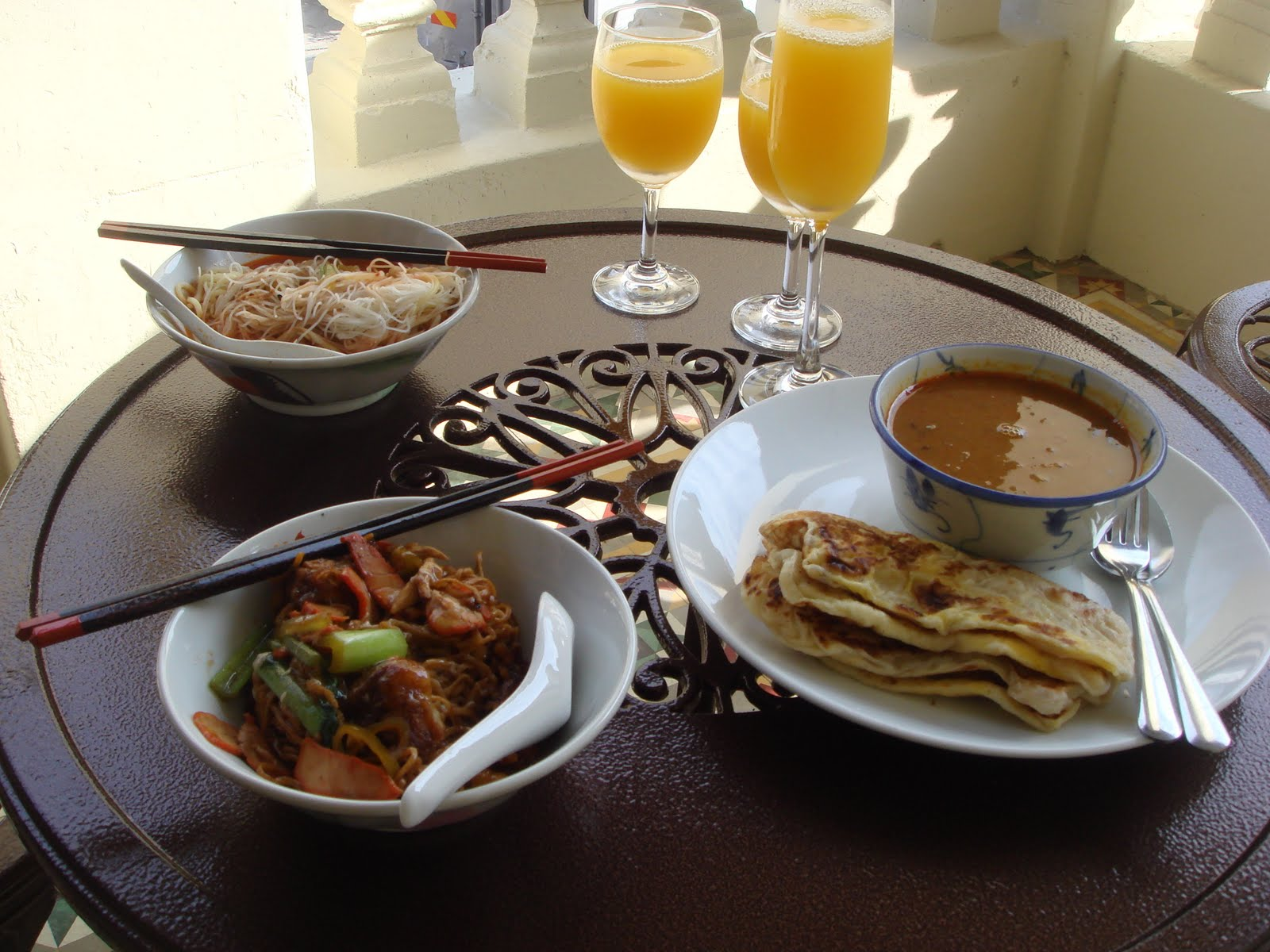 A mixture of Indian food (naan and curry) and Chinese food (noodles) for breakfast