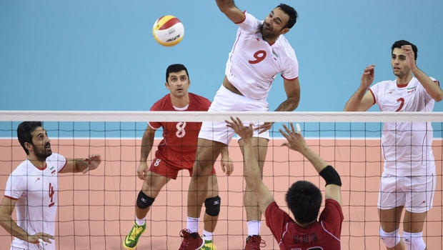 Iran's Adel Gholami (C) smashes the ball at Japan's defenders during the men's volleyball final match for the 17th Asian Games between Japan and Iran at the Songnim Gymnasium in Incheon on 3 October 2014.