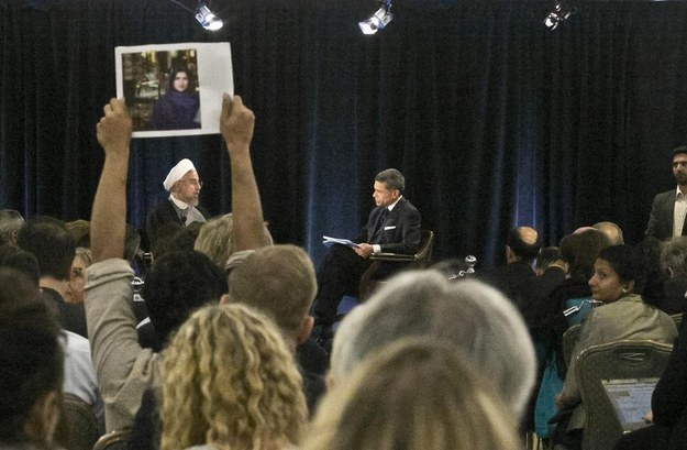 A protester holds up a picture of Ghoncheh Ghavami as Iran's President Dr. Hassan Rouhani, left, speaks with moderator Fareed Zakaria at New America, a public policy institute and think tank in New York on Wednesday.