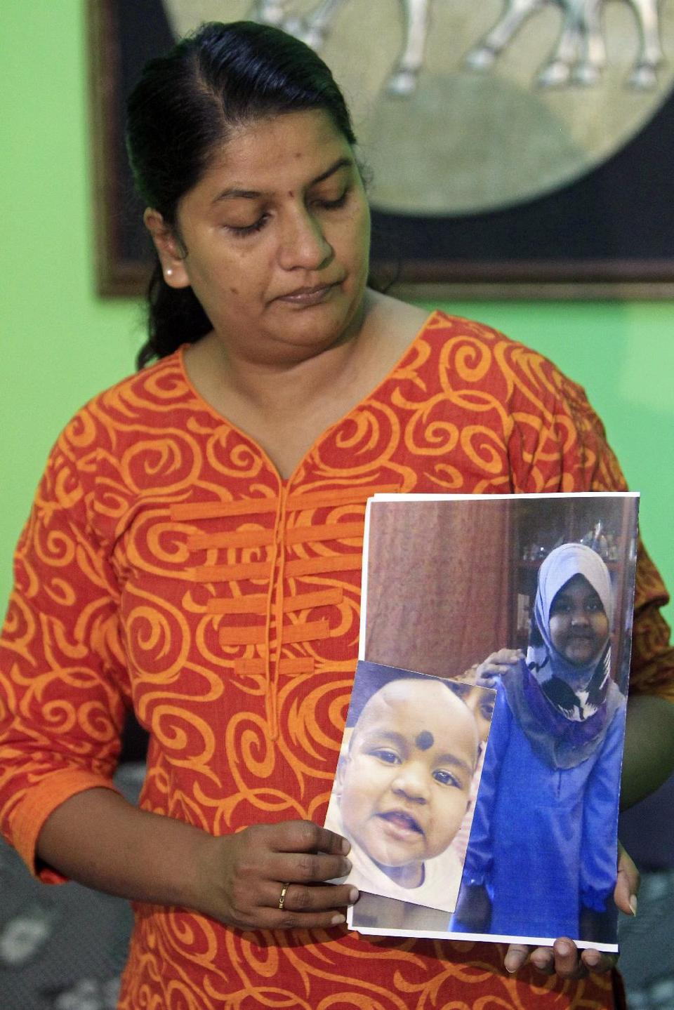 In this 16 October 2014 photo, M. Indira Gandhi shows photos of her youngest daughter Prasana Diksa during an interview at her house in Ipoh