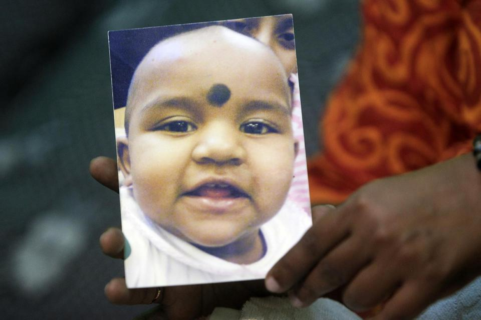M. Indira Gandhi holds a photo of her youngest daughter Prasana Diksa