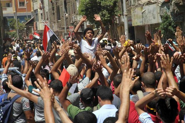 Egyptian supporters shout slogans during a rally to mark the first anniversary of the military overthrow of Islamist president Mohamed Morsi, in Cairo's Mattarya district on 3 July  2014