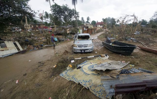 A villager's car left stranded and broken surrounded by mud and debris.