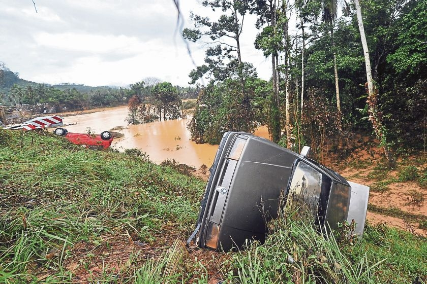 An overturned car washed away by the floods lies on the banks of Sungai Lebir.