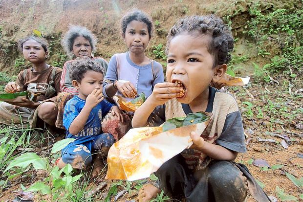 Orang asli children finally getting some food after supplies were delivered by helicopter to an area near their inundated village in Gua Musang.