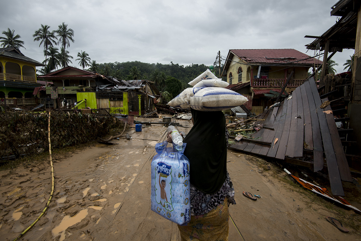 A villager carrying donated rice and other necessities as she looks at the damaged caused by the flood in Kampung Manek Urai Lama.