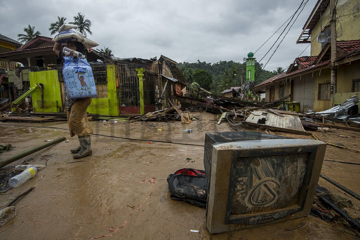 A victim of the devastating east coast floods is seen here carrying aid in the town of Manik Urai in Kelantan, as the waters seem to have receded on 30 December.
