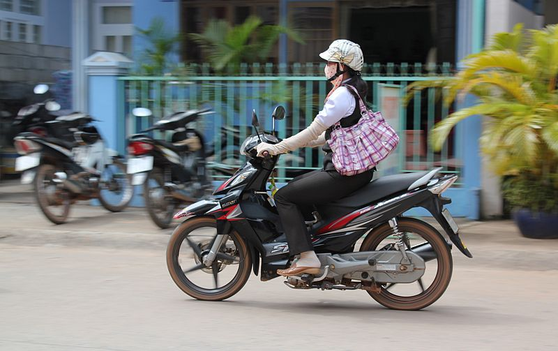 A Vietnamese motorcyclist wears long gloves to block the sun, despite the tropical heat.