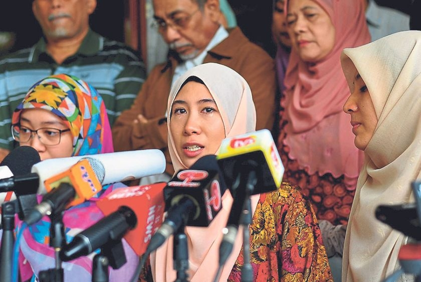Nurul Nuha in tears as she speaks to the media at her family residence in Bukit Segambut yesterday. With her are sisters Nurul Izzah (right) and Nurul Iman.
