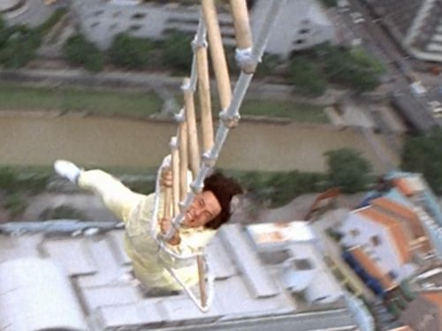 Jackie Chan hanging on a rope ladder while flying across KL.