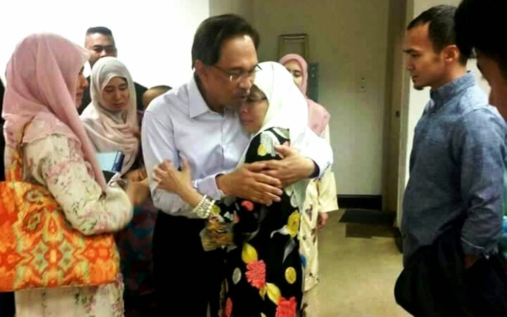Opposition leader Datuk Seri Anwar Ibrahim (right) will be serving a five-year jail term for sodomy. (Pic inset) Anwar embraces his wife,  Wan Azizah Wan Ismail to comfort her.