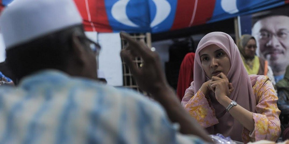 PKR vice-president Nurul Izzah listens intently to one of the party members in Permatang Pauh during a meet-the-people session.
