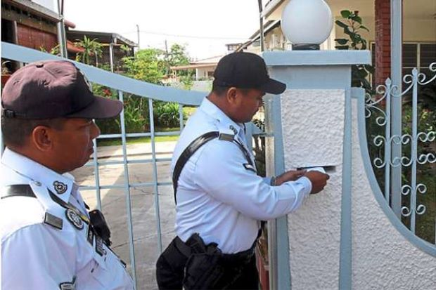 Nailed: Two police officers leaving a warrant of arrest at the house of a traffic offender in Malacca during Ops Warta last year. They will be launching the operation again next month.