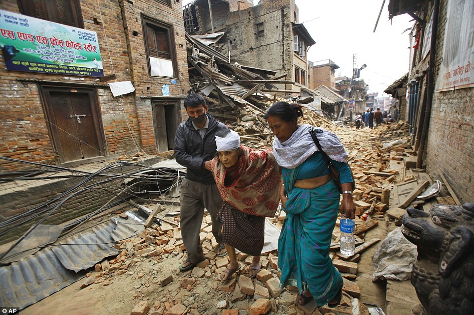 An elderly woman is accompanied through the street in the Bhaktapur after undergoing treatment for a head injury at one of its remaining hospitals.