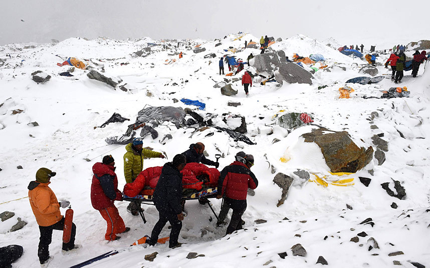 Here, rescuers use a makeshift stretcher to carry an injured person after an avalanche triggered by an earthquake flattened parts of Everest Base Camp