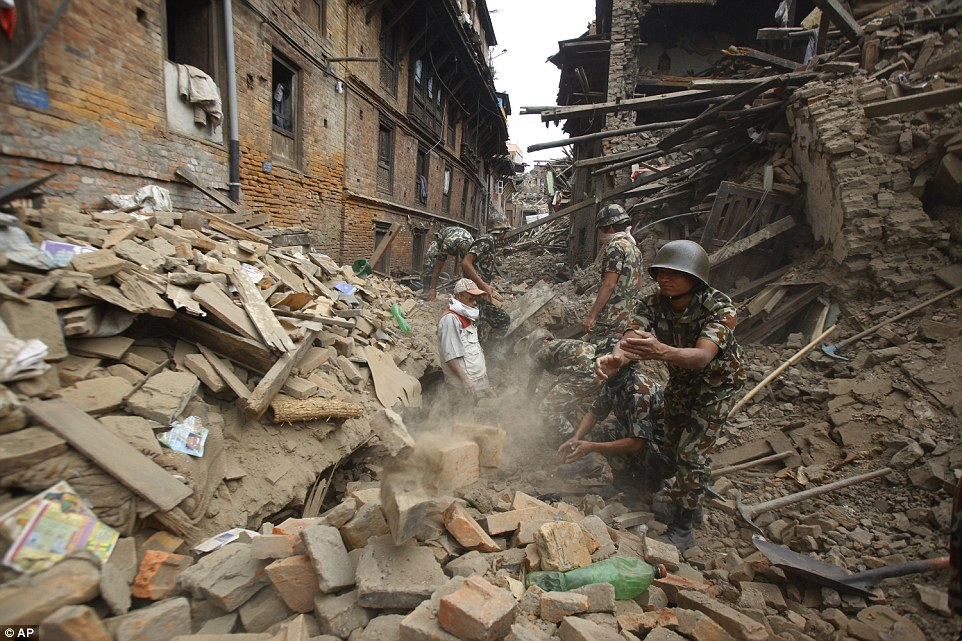 Aid workers use their hands to dig bricks from piles of rubble in Bhaktapur as more relief arrives from neighbouring countries on Sunday.