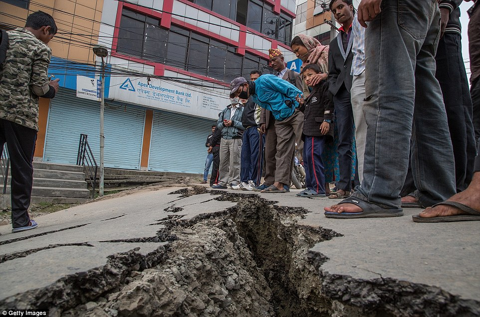 Survivors inspect a crack in the road left in Kathmandu, Nepal, in the wake of the earthquake.