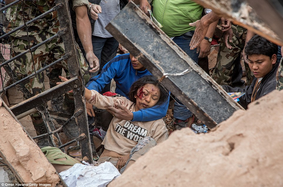 A survivor is pulled from the rubble of a collapsed building in Kathmandu yesterday shortly after the earthquake struck at around noon.