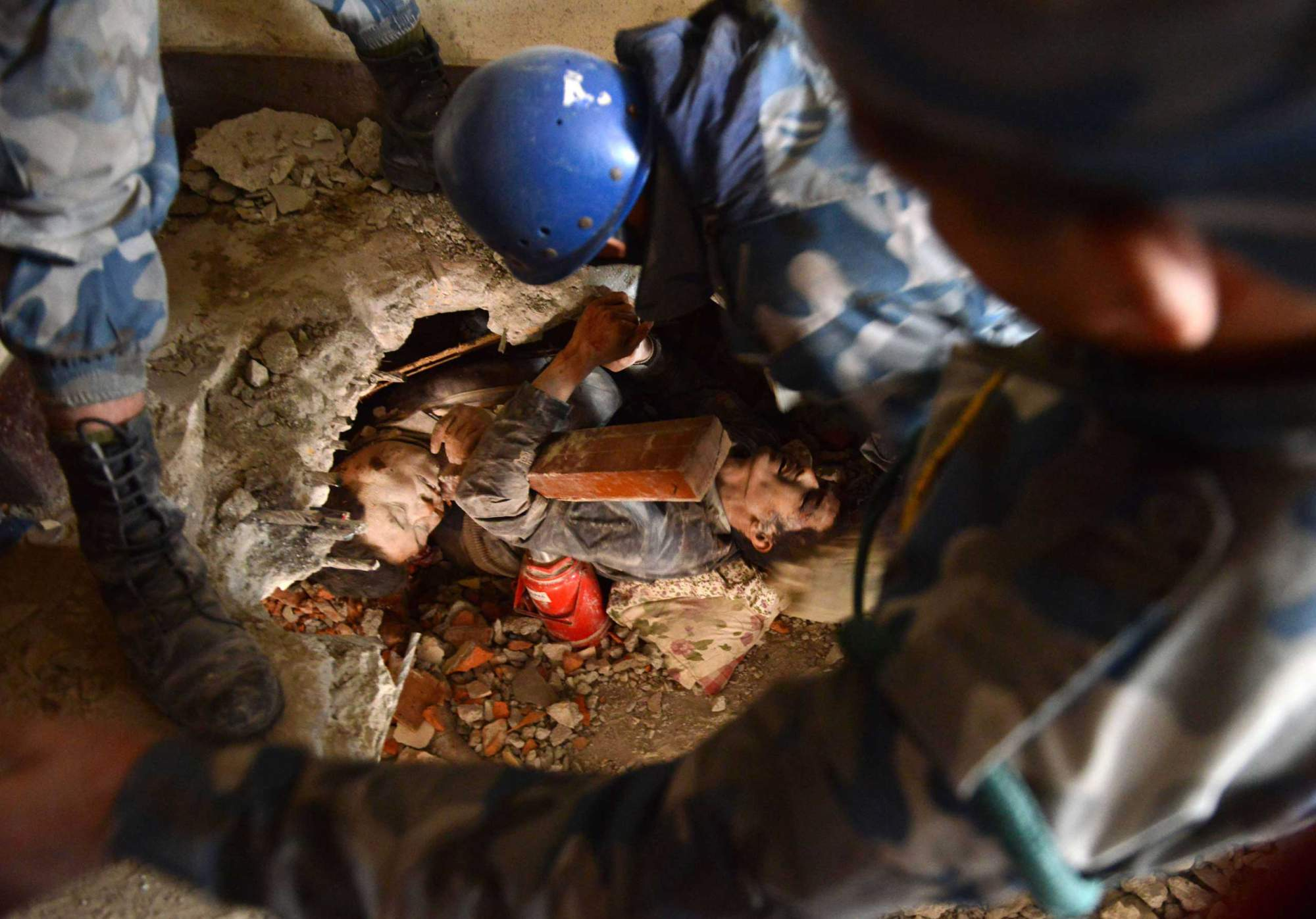 Nepalese rescue personnel help a trapped earthquake survivor, center right, as his friend lies dead next to him in Swayambhu, in Kathmandu on April 26, 2015.