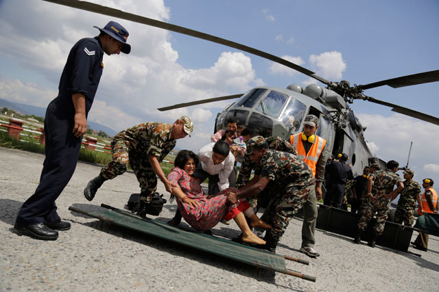 A woman injured in Saturday's earthquake is laid on a stretcher after being evacuated in an Indian Air Force helicopter at the airport in Kathmandu, Nepal, on Monday.