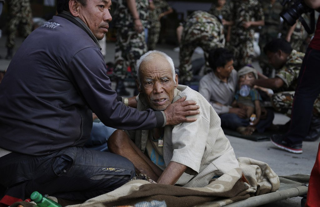 A Nepalese man attends to an elderly as victims of Saturday's earthquake, wait for ambulances after being evacuated at the airport in Kathmandu, Nepal, Monday.