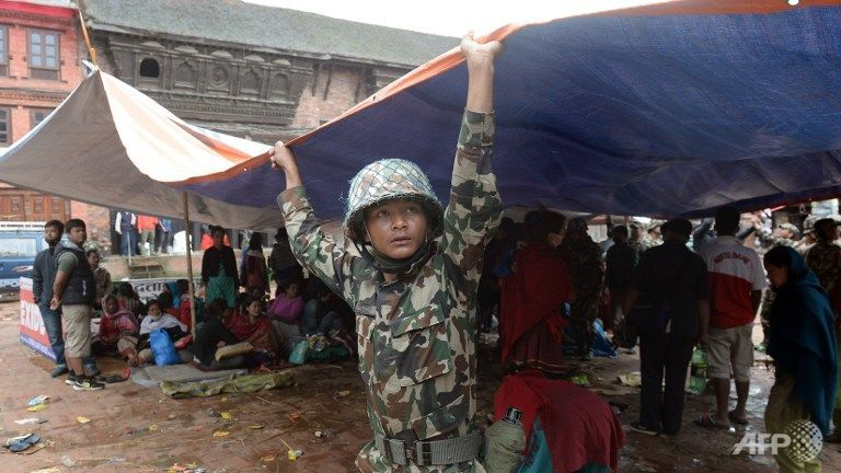 A member of the Nepalese security forces sets up a tent in Bhaktapur on the outskirts of Kathmandu on April 26, 2015.