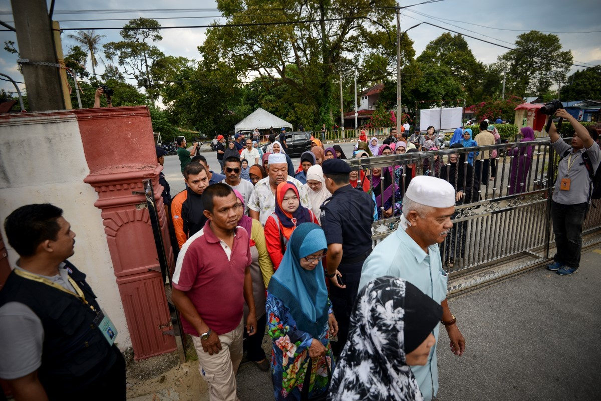 Permatang Pauh voters entering the SMK Guar Perahu voting centre today. The Permatang Pauh by-election sees a four-cornered fight involving Suhaimi Sabudin from Barisan Nasional, Dr Wan Azizah Wan Ismail (PKR), Azman Shah Othman (PRM) and Salleh Isahak (independent).
