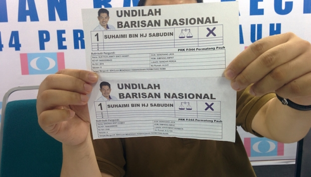 Rafizi holds up voting slips showing the information of the purported phantom voters.