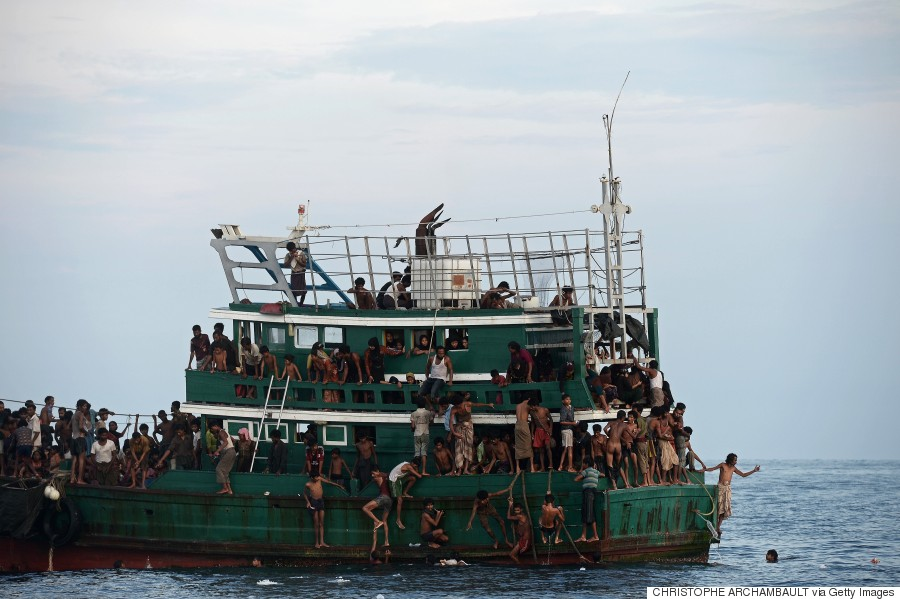 Rohingya migrants bring back food supplies dropped by a Thai army helicopter after jumping to collect them at sea on 14 May 2015.