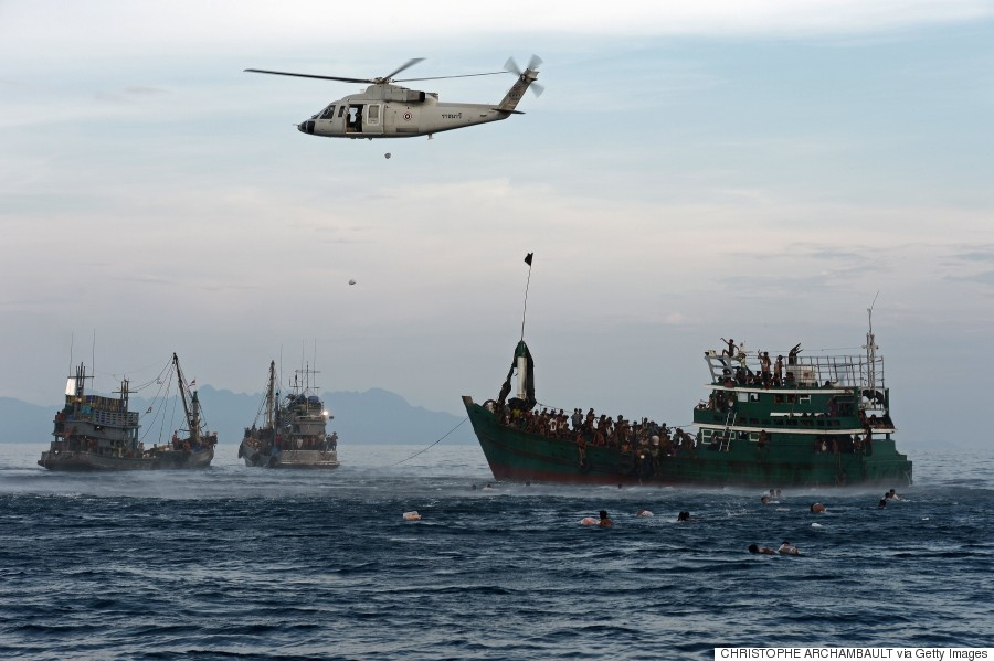 Rohingya migrants swim to collect food supplies dropped by a Thai army helicopter after they jumped off a boat drifting in Thai waters off the southern island of Koh Lipe, 14 May 2015.