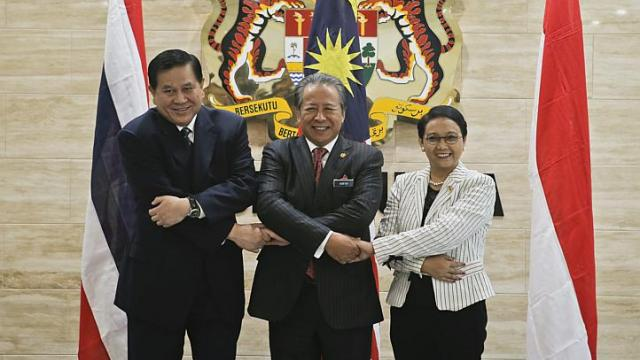 Ministers of Foreign Affairs from Thailand, Mr Tanasak Patimapragorn (left), Malaysia, Datuk Seri Anifah Aman (centre), and Indonesia, Ms Retno Marsudi (right) holding hands during a meeting on human trafficking and people smuggling in Putrajaya, Malaysia on May 2015.