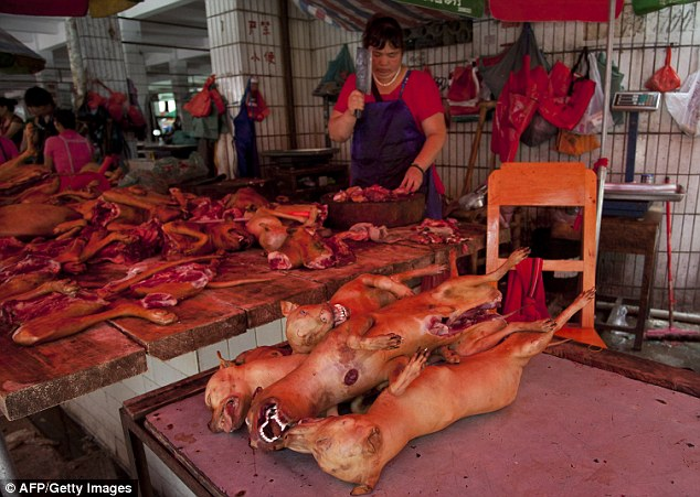 This picture taken on June 17, 2015 shows a butcher preparing cuts of dog meat for sale in Yulin.