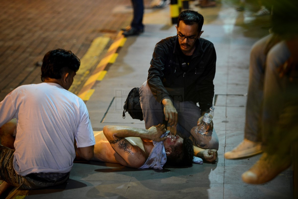 An injured man is seen being tended to outside Low Yat Plaza.