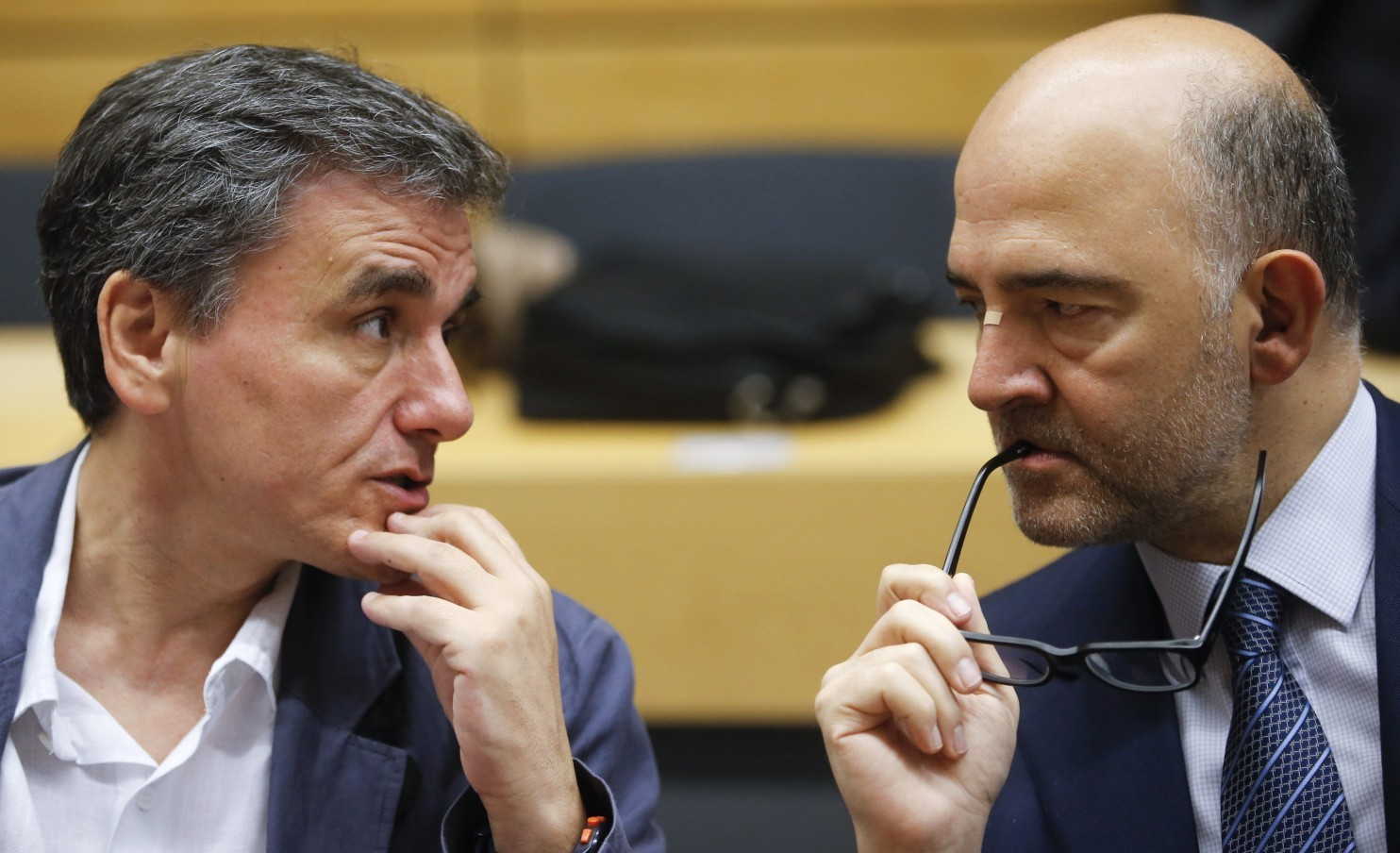 Greek Finance Minister Euclid Tsakalotos talks to European Economic and Financial Affairs Commissioner Pierre Mocovici (R) during a euro zone finance ministers meeting in Brussels, Belgium, July 12, 2015.