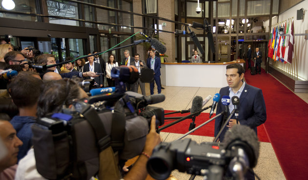 "Greek Prime Minister Alexis Tsipras, right, speaks with the media on Monday, July 13, 2015 after a summit of eurozone leaders reached a tentative agreement with Greece for a bailout program that includes ""serious reforms"" and aid."
