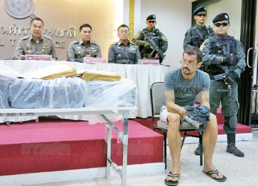 Xavier Justo (grey shirt) surrounded by Thai poliec during his arrest.
