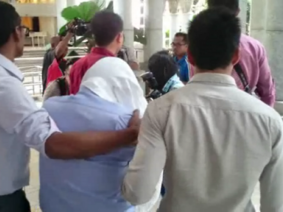 Screen capture of the video showing MACC officers escorting Ihsan Perdana's managing director (second from left) out of Putrajaya Magistrate Court.