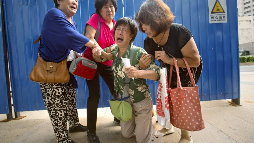 ao Lanfang, second from right, whose daughter-in-law, son, and granddaughter were aboard Malaysia Airlines Flight 370, kneels in grief while speaking to journalists outside the company's offices in Beijing, Thursday, Aug. 6, 2015.