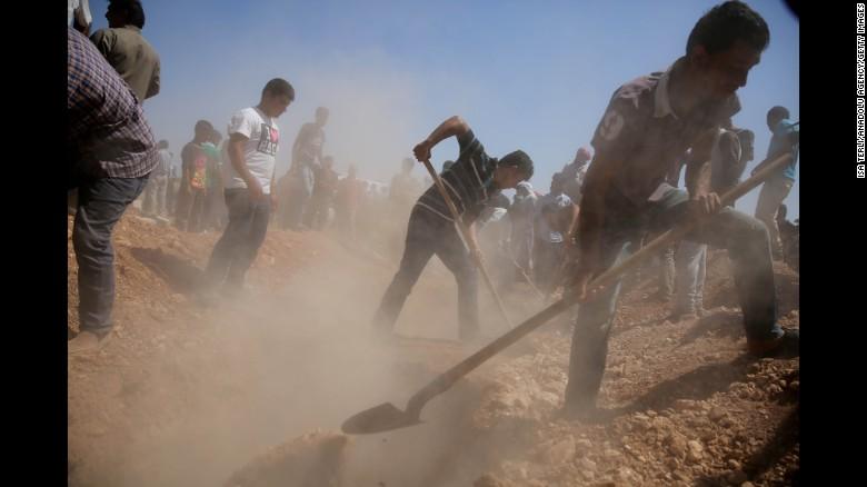 Men digging grave for the little Aylan.