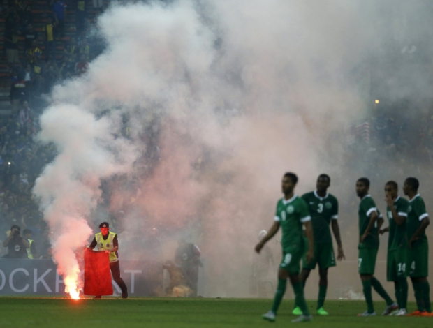 A police officer extinguishes a flare on the pitch thrown by angry fans