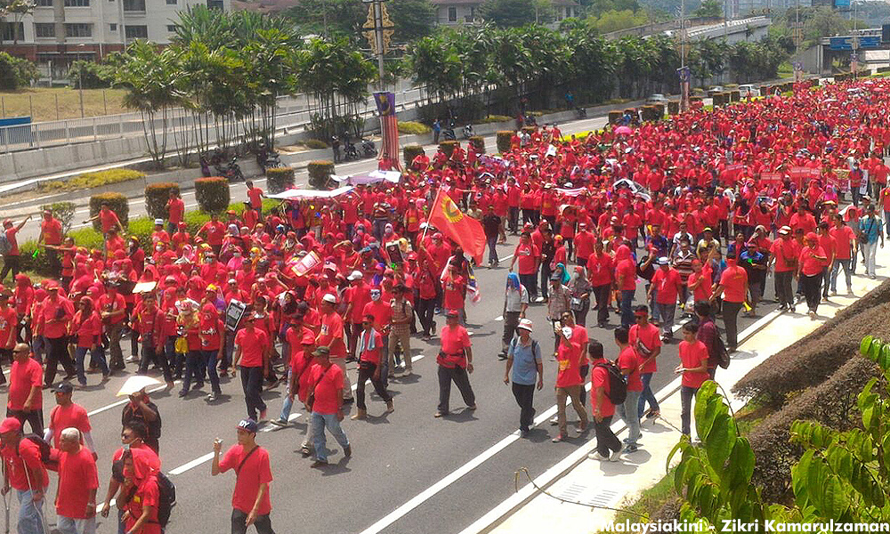 Protesters marching towards Padang Merbok with racially instigated placards