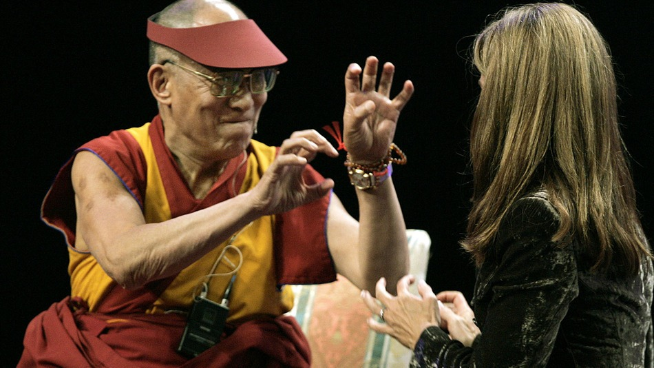 The Dalai Lama describes how he used his fingernails as weapons when, at the age of 4, he got into a spat with his brother as Maria Shriver, wife of California Governor Arnold Schwarzenegger, listens on stage at the California Governor and First Lady's Conference on Women in Long Beach, California, on 26 September, 2006.