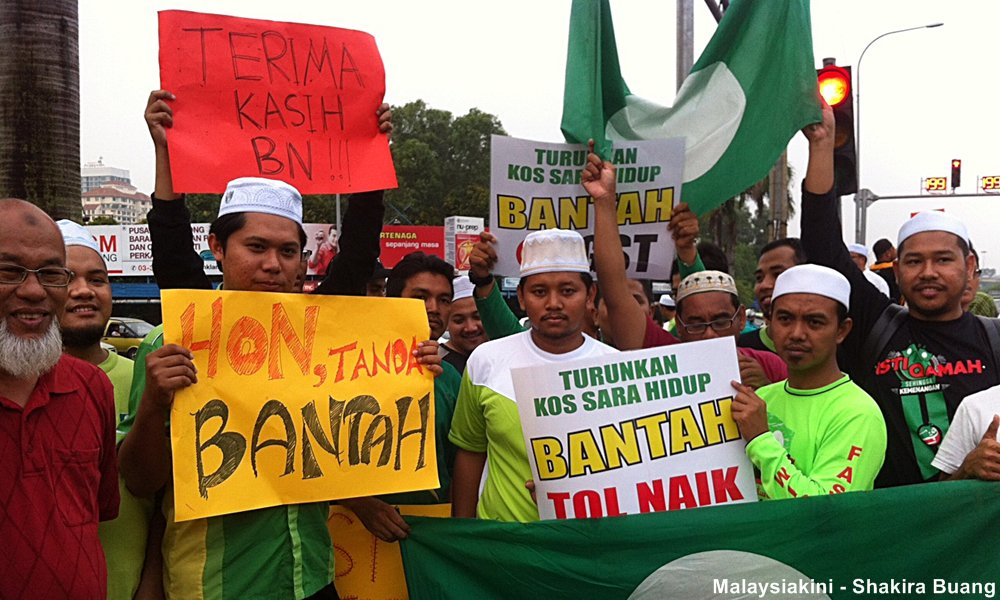 "Selangor PAS Youth led protest saw protesters holding placards that read, 'Turunkan Kos Sara Hidup, Bantah Tol Naik"" (Reduce the cost of living, we are against the toll hike), ""Terima kasih BN"" (Thank you, BN) among others"